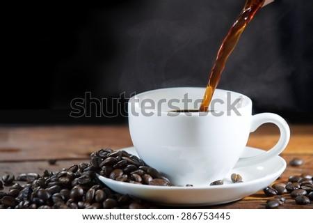 Pouring coffee with smoke smoldering. - stock photo