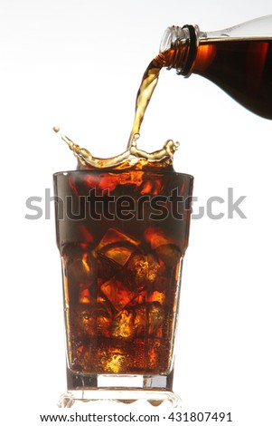pouring cola drinks to a glass with ice cubes