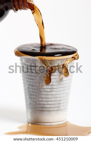 Pouring cola from bottle into overflowing plastic cup. Isolated on white background.