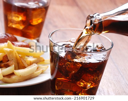 pouring cola in glass beaker - stock photo