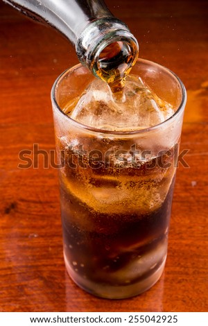 Pouring cola into the glass on wooden table. - stock photo