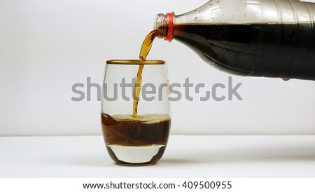 Pouring  cola or soda from the bottle into a glass on white background - stock photo