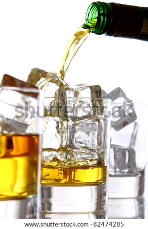 Pouring cold whiskey into the glass isolated over white background