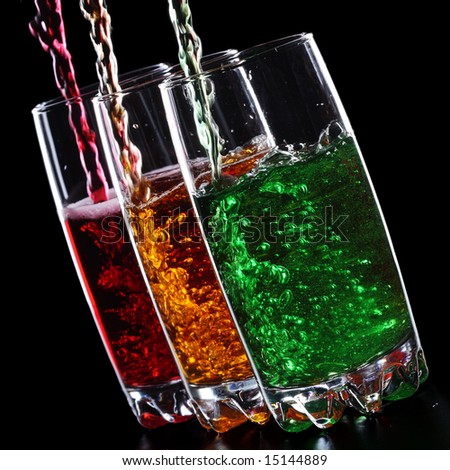 Pouring colorful sparkling drinks isolated on black background