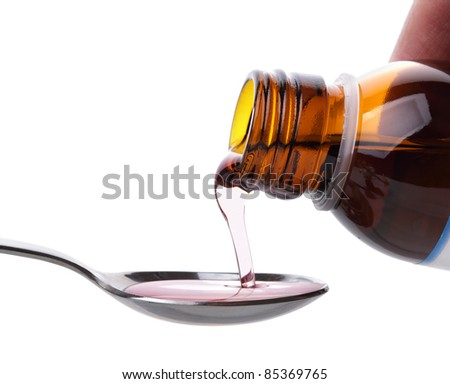 Pouring cough medicine onto a spoon from a bottle