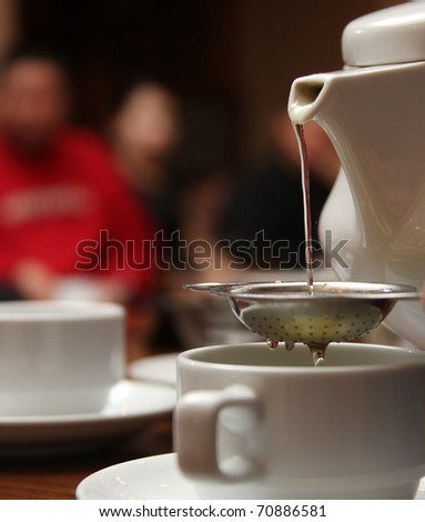 pouring darjeeling tea from a white tea pot into a cup and saucer through a silver tea strainer - stock photo