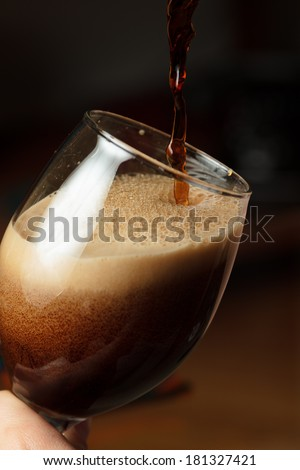 Pouring dark beer - high contrast - stock photo