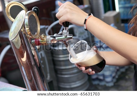 Pouring dark beer to plastic glass from beer tap