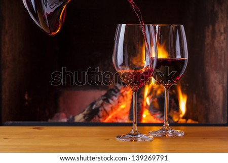 pouring delicious red wine at romantic fireplace - stock photo