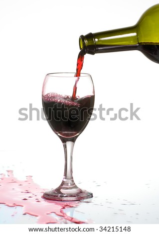 Pouring delicious red wine in a glass with reflection and spill. - stock photo