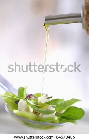 Pouring french dressing onto a mixed salad with diced goat's cheese - stock photo