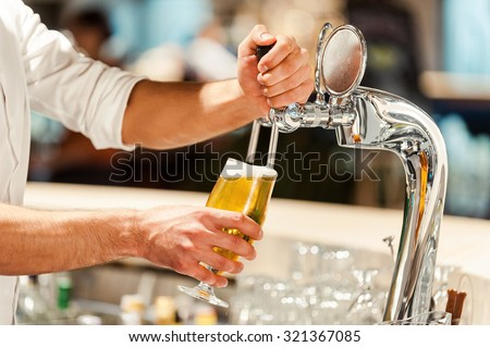 Pouring fresh beer. Close-up of young bartender pouring beer while standing at the bar counter - stock photo