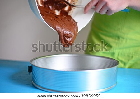 Pouring fresh chocolate cream in metal mould for cake - stock photo
