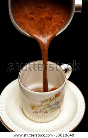 Pouring fresh Greek Turkish coffee into a cup (isolated on black) - stock photo