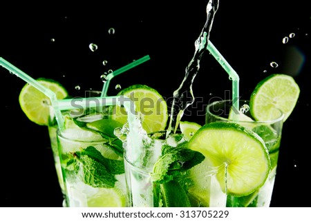 Pouring fresh mojito cocktail in glasses isolated on black background - stock photo
