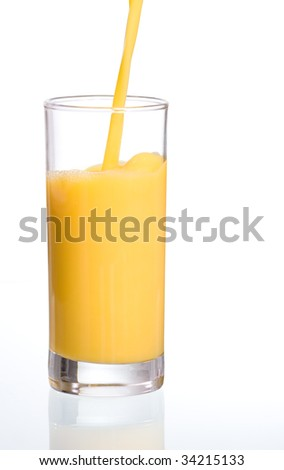 Pouring fresh orange juice in a glass with reflection