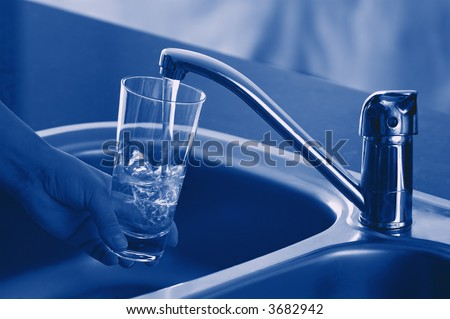 Pouring Fresh Tap Water Into a Glass. Shallow DOF. Focus on Tap. - stock photo