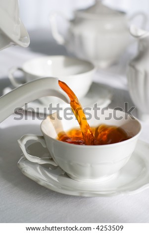 Pouring fresh tea from porcelain tea kettle into white cup. Focus on tea stream, shallow depth of field. - stock photo