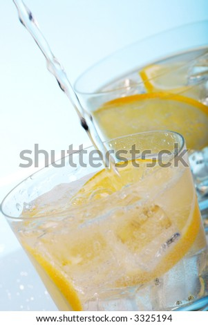 Pouring fresh water into one of two glasses with cocktails, sliced lemon and ice cubes over aqua paper background - stock photo