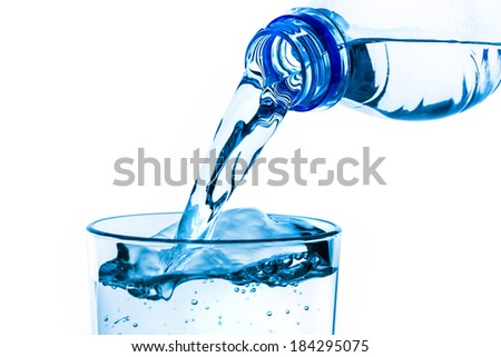 pouring fresh water into the glass from a plastic bottle on white background