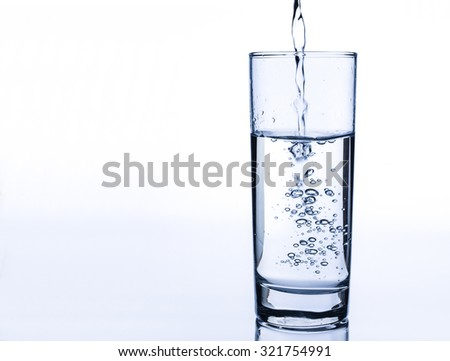 Pouring fresh water on glass on light background. - stock photo