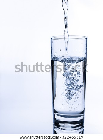 Pouring fresh water on glass on light background.