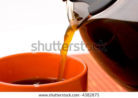 Pouring freshly brewed coffee from a pot to a coffee cup - stock photo