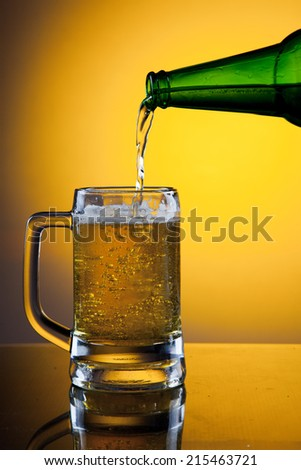 Pouring full mug of beer on golden background