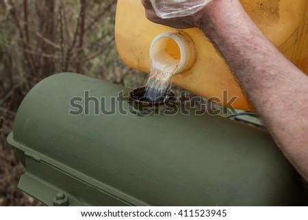 pouring gasoline into the gas tractor cultivating tank from a  canister - stock photo