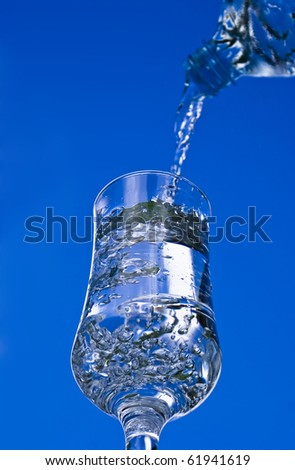 Pouring glass of water on the blue sky background
