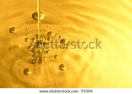 Pouring golden liquid - golden toned water. - stock photo