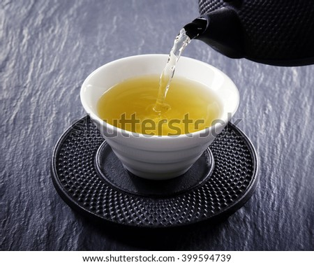 Pouring green tea into white pialat on slate plate background - stock photo