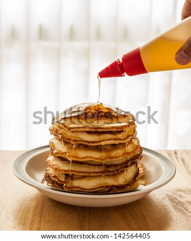 Pouring Honey onto Pancakes on Dish - stock photo
