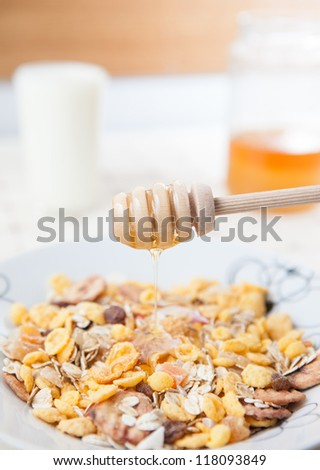 Pouring honey over cornflakes - stock photo