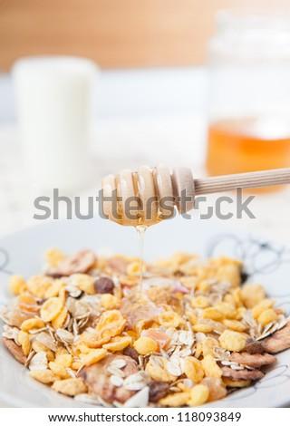 Pouring honey over cornflakes - stock photo