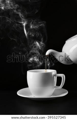 Pouring hot tea from a kettle into a cup on black background, close up - stock photo