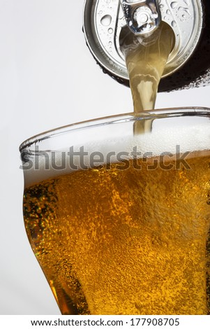 Pouring ice cool beer from a ring pull can - stock photo