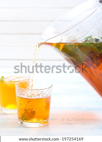 Pouring ice tea with mint into the glass - stock photo