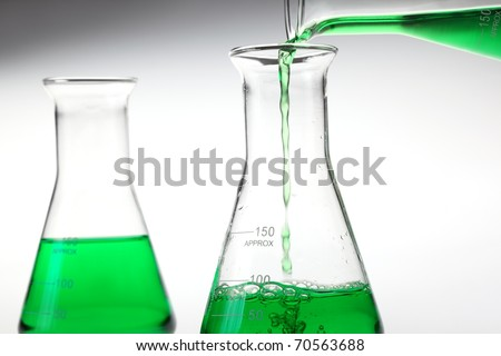 Pouring liquid chemicals into flask . - stock photo
