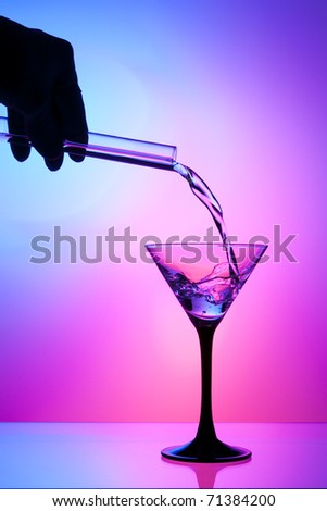 Pouring liquid from a flask into a cocktail / martini glass - stock photo