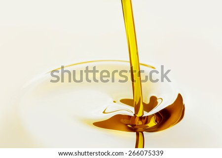 Pouring liquid golden oil close up view - stock photo