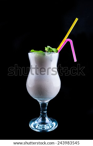 Pouring liquor in glass isolated on black - stock photo