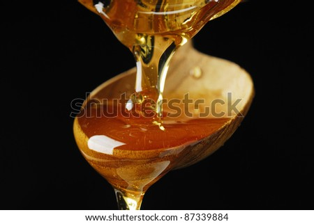 Pouring Maple Syrup over a Spoon - stock photo