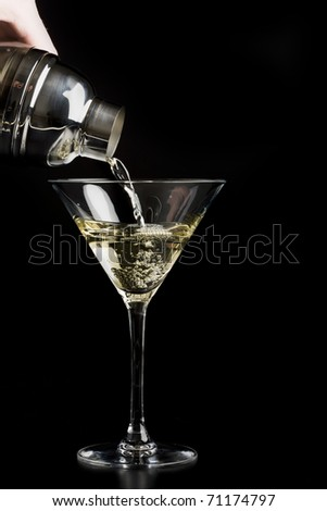 Pouring martini into martini glass - stock photo