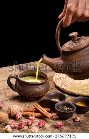 Pouring masala tea from dark ceramic pot - stock photo