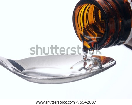 Pouring medicine syrup detail on a teaspoon. - stock photo