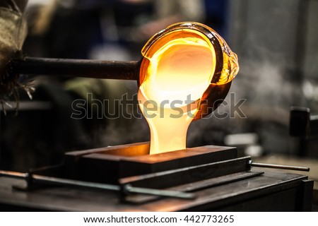 Pouring Melted Glass into Graphite Mold in Workshop - stock photo