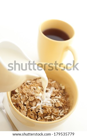 Pouring milk from a ceramic jug into a bowl of nutritional breakfast cereal or muesli with a freshly brewed mug of espresso coffee alongside - stock photo