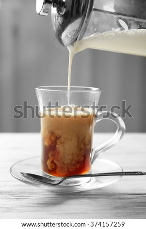 Pouring milk in coffee on light wooden table