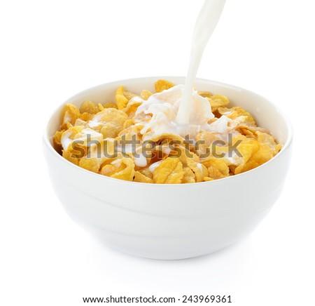 pouring milk into cornflakes bowl isolated on white - stock photo